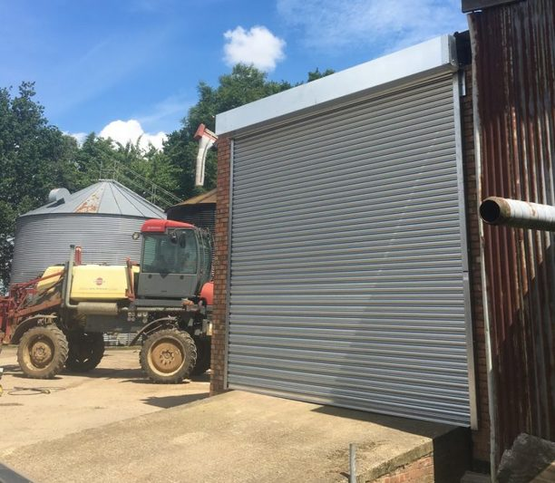 Roller shutter door installed on small building within an outdoor work area with outdoor work area
