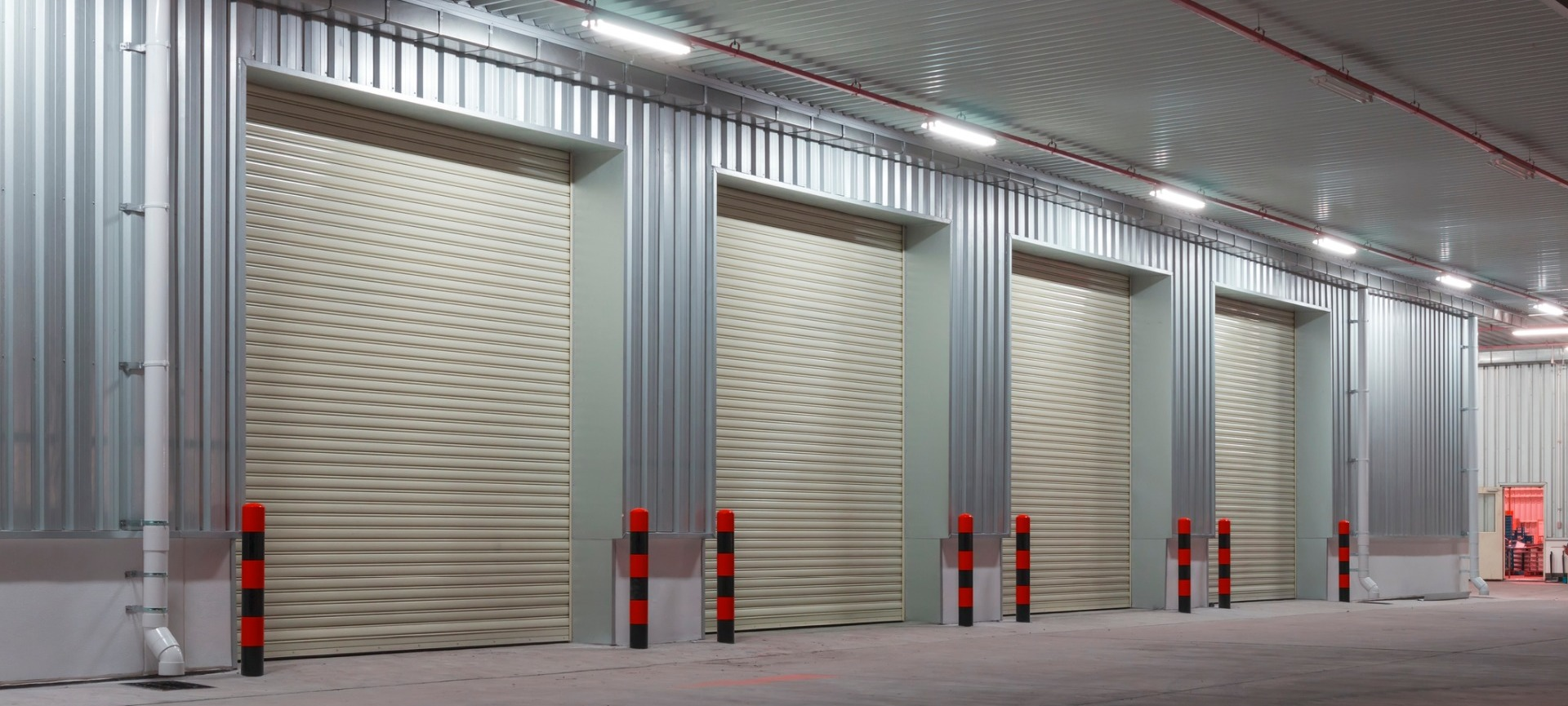 Warehouse with nightlights and protective pillars outside four shutter doors to keep each vehicle separate for each department, delivery to and from warehouse