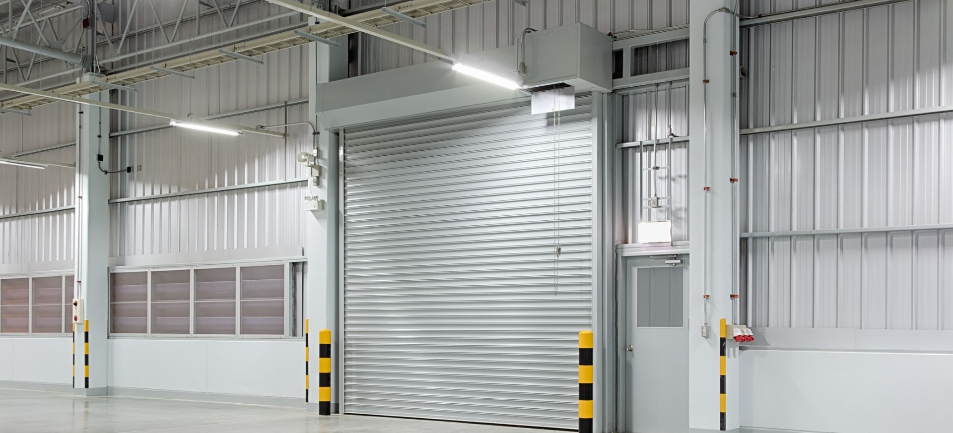 Large metal roller shutter door on inside of clean and clear warehouse with yellow and back striped bollards
