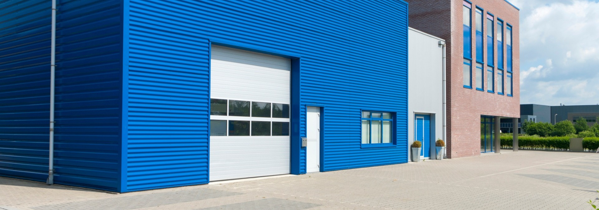 Blue metal sheet building that has a white industrial sectional door with 2 rows of 4 glass pane windows featured on door. Entrance door one foot away