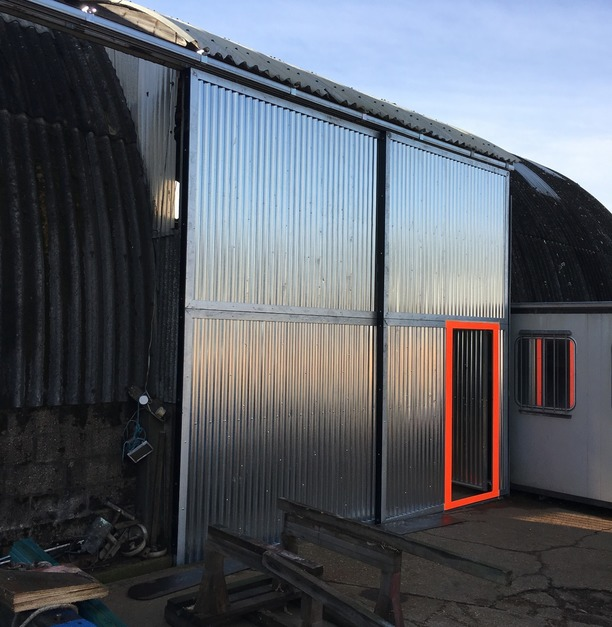 Metal sheet walls with an orange rimmed door for easy access