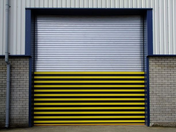 Multicoloured shutter door on warehouse. Top half with clear grey metal stripes, the bottom half with black and yellow bumble-bee style stripes