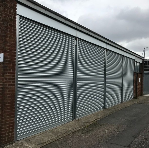 Industrial Roller shutter door installed on small building within an outdoor work area with outdoor work area